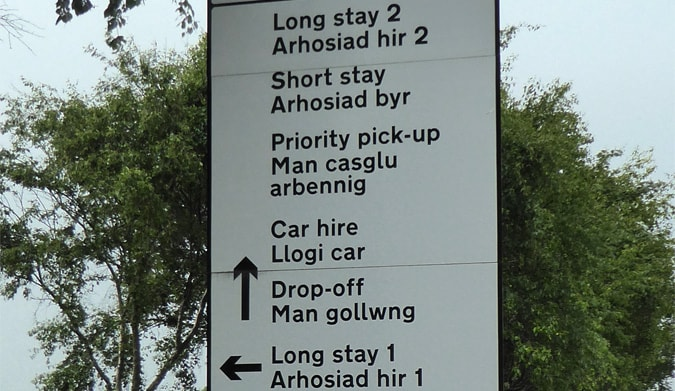 Multi-language signage with dual Welsh and English in an airport in Wales.